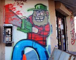 Graffiti - Lumberjack sawing through pay telephone