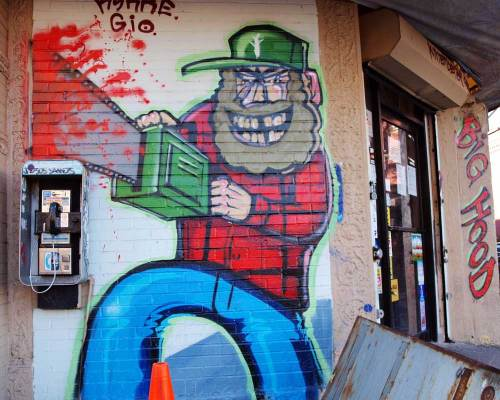Graffiti - Lumberjack sawing through pay telephone