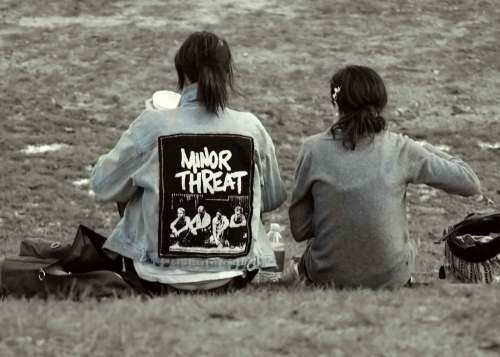 Women with Minor Threat jacket on lawn in Cental Park